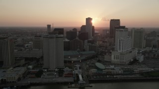 AX61_064 - 5K stock footage aerial video pass riverfront hotels and skyscrapers in Downtown New Orleans with the setting sun in the background, Louisiana
