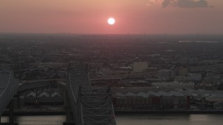 AX61_069 - 5K stock footage aerial video of the setting sun seen from Crescent City Connection Bridge at sunset, New Orleans, Louisiana