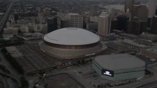 AX61_076 - 5K stock footage aerial video orbit the Superdome and New Orleans Arena at sunset, Downtown New Orleans, Louisiana