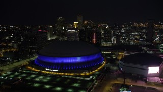 AX62_002 - 5K stock footage aerial video of reverse view of the Superdome, New Orleans Arena, and skyscrapers at night, Downtown New Orleans, Louisiana