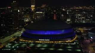 AX62_005 - 5K stock footage aerial video approach Superdome and skyscrapers at night, Downtown New Orleans, Louisiana