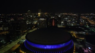 AX62_006 - 5K stock footage aerial video fly over the Superdome at night and approach skyscrapers in Downtown New Orleans, Louisiana
