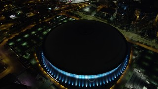 AX62_012 - 5K stock footage aerial video orbit the Superdome at night as lights change color, Downtown New Orleans, Louisiana