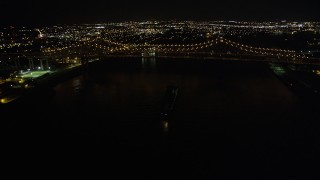 AX62_015 - Aerial stock footage of 5K aerial  video of cargo ship sailing under Crescent City Connection Bridge at night, New Orleans, Louisiana