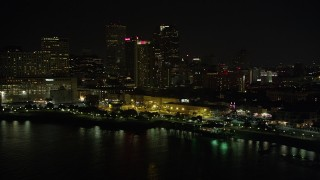 AX62_030 - 5K stock footage aerial video of Downtown New Orleans skyscrapers seen from the Mississippi River at night, Louisiana