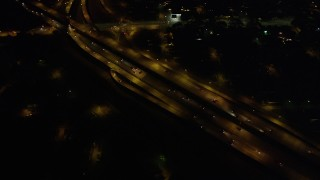 AX62_049 - 5K stock footage aerial video of reverse and bird's eye view of freeway interchange at night, New Orleans, Louisiana