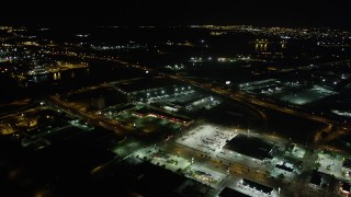 AX62_050 - 5K stock footage aerial video reverse view of a strip mall by the Danziger and I-10 High Rise Bridges at night, New Orleans, Louisiana
