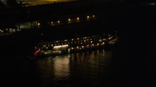 AX63_007 - 5K stock footage aerial video of tracking Natchez Steamboat on Mississippi River at night, French Quarter, New Orleans, Louisiana