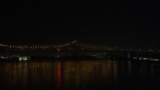 AX63_011 - 5K stock footage aerial video track and ambulance crossing Crescent City Connection Bridge at night, New Orleans, Louisiana