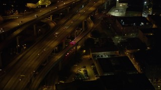AX63_012 - 5K stock footage aerial video track an ambulance exiting the Crescent City Connection Bridge at night, New Orleans, Louisiana