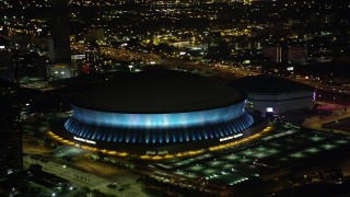 AX63_020 - 5K stock footage aerial video orbit the Superdome as it changes colors at night, New Orleans, Louisiana