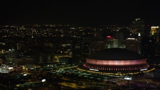 AX63_022 - 5K stock footage aerial video of lighting change at the Superdome near Downtown New Orleans skyscrapers at night, Louisiana