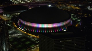 AX63_025 - 5K stock footage aerial video orbit the Mercedes-Benz Superdome at night and the lights change colors, Downtown New Orleans, Louisiana