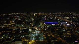 AX63_027 - 5K stock footage aerial video of a reverse view  Superdome and Downtown New Orleans at night in Louisiana