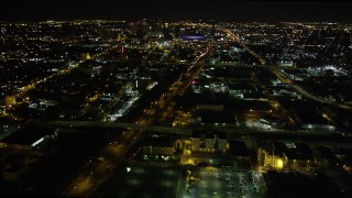 AX63_038 - 5K stock footage aerial video pan across I-10 in Mid-City to reveal and approach Downtown New Orleans at night, Louisiana