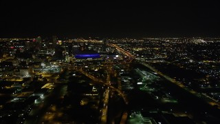 AX63_039 - 5K stock footage aerial video follow Interstate 10 to the interchange and the Superdome at night in Downtown New Orleans, Louisiana