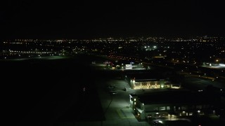 AX63_049 - 5K stock footage aerial video flyby neighborhoods in New Orleans East to reveal Lakefront Airport at night, Louisiana
