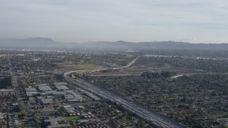 AX64_0001 - 5K stock footage aerial video of I-5 / 170 split by warehouse buildings and suburban homes in Pacoima, California