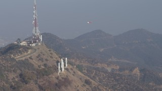 AX64_0016 - 5K stock footage aerial video of emergency helicopter landing at Hollywood Sign, Los Angeles, California