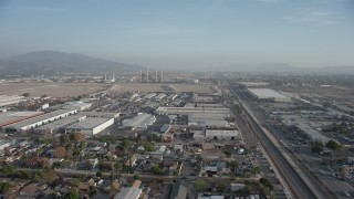 AX64_0044 - 5K stock footage aerial video fly over homes and warehouses to approach power plant smoke stacks, Sun Valley and Pacoima, California