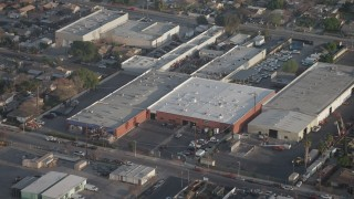AX64_0054 - 5K stock footage aerial video approach and tilt to warehouse buildings in Sun Valley, California