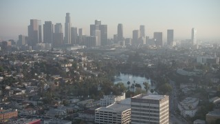 AX64_0078 - 5K stock footage aerial video of an approach to Echo Park and hazy Downtown Los Angeles skyline, California