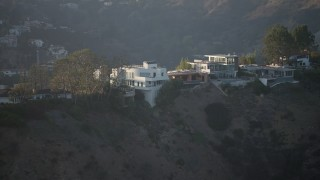AX64_0122 - 5K stock footage aerial video flyby mansions in Hollywood Hills, California sunset