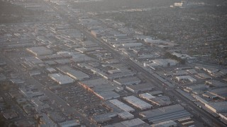 AX64_0134 - 5K stock footage aerial video of warehouses and Sherman Way Square mall beside train tracks in North Hollywood, California, sunset