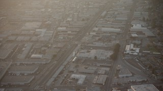 AX64_0135 - 5K stock footage aerial video of warehouse buildings and railroad tracks in North Hollywood, California, sunset