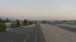 AX64_0142 - 5K stock footage aerial video of lifting off from Whiteman Airport runway, Pacoima, California, Sunset