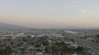 AX64_0143 - 5K stock footage aerial video fly over warehouses to approach LADWP power plant in Pacoima, California, sunset