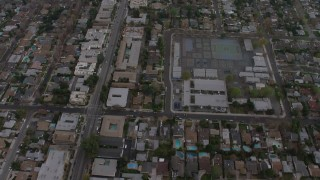 AX64_0153 - 5K stock footage aerial video bird's eye view of suburban neighborhoods and an elementary school, Van Nuys, California, twilight
