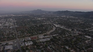 AX64_0155 - 5K stock footage aerial video approach residential neighborhoods beside Tujunga Wash, Valley Village, California, twilight