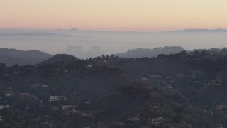 AX64_0156 - 5K stock footage aerial video of Century City behind hilltop mansions in Hollywood Hills, California, twilight