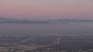 AX64_0158 - 5K stock footage aerial video of Santa Susana Mountains and neighborhoods in San Fernando Valley, Los Angeles, California, twilight