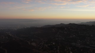 AX64_0162 - 5K stock footage aerial video of passing hillside mansions in Hollywood Hills, California, twilight