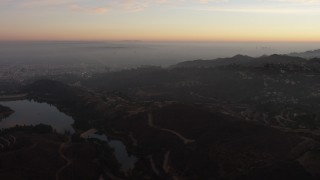 AX64_0163 - 5K stock footage aerial video flyby hillside mansions in Hollywood Hills and reveal Hollywood Reservoir, California, twilight