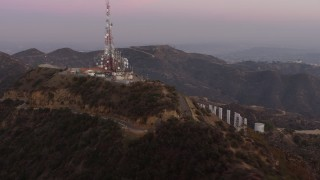 AX64_0164 - 5K stock footage aerial video of radio tower above Hollywood Sign, Los Angeles, California, twilight
