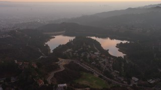 AX64_0168 - 5K stock footage aerial video of Hollywood Reservoir and Mulholland Dam in Los Angeles, California, twilight