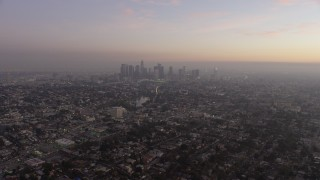 AX64_0179 - 5K stock footage aerial video of Downtown Los Angeles surrounded by city sprawl, California, twilight