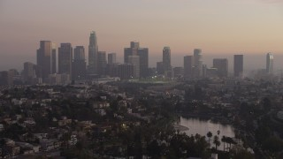 AX64_0181 - 5K stock footage aerial video of Downtown Los Angeles in haze seen from Echo Lake at twilight, California