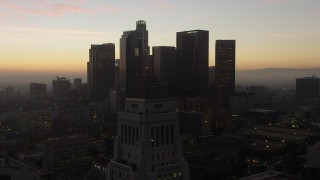 AX64_0192 - 5K stock footage aerial video flyby the top of City Hall for a view of Downtown Los Angeles skyline, California, twilight
