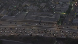 AX64_0199 - 5K stock footage aerial video of a police helicopter flying over 110 freeway traffic in Downtown Los Angeles, California, twilight