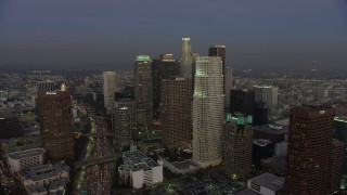 AX64_0206 - 5K stock footage aerial video follow 110 freeway toward Downtown Los Angeles skyscrapers, California, twilight