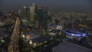 AX64_0223 - 5K stock footage aerial video of 110 Freeway, Staples Center arena, and Downtown Los Angeles skyscrapers, California, twilight