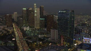AX64_0224 - 5K stock footage aerial video of 110 Freeway, Downtown Los Angeles skyscrapers, The Ritz-Carlton, California, twilight