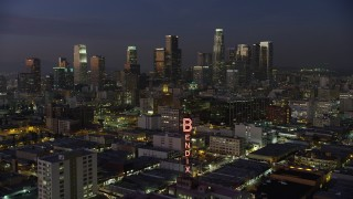 AX64_0244 - 5K stock footage aerial video approach Bendix Sign and Downtown Los Angeles skyscrapers, California, twilight