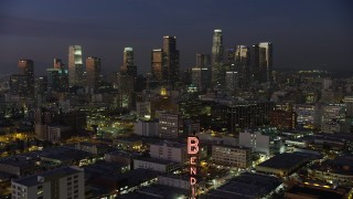 AX64_0245 - 5K stock footage aerial video fly over the Bendix Sign to fly toward Downtown Los Angeles skyscrapers, California, twilight