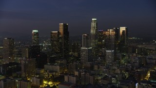 AX64_0246 - 5K stock footage aerial video fly over Eastern Columbia Building to approach Downtown Los Angeles skyscrapers, California, twilight