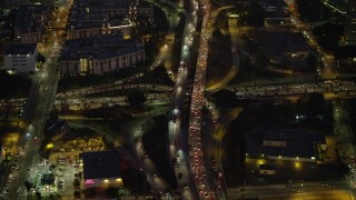 AX64_0253 - 5K stock footage aerial video of reverse view of heavy traffic on 101 and 110 freeways in Downtown Los Angeles, California, Night